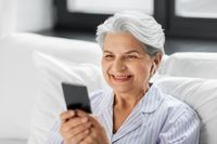 senior woman with smartphone and earphones in bed
