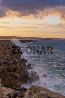 Peniche lighthouse with Supertubos beach on the background at sunset with waves crashing, in Portugal