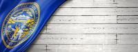 Nebraska flag on white wood wall banner, USA