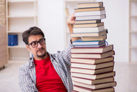 Young male student and too many books in the classroom