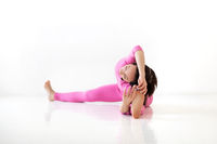 Young slender fit woman in pink long bodysuit performing yoga pose, isolated over white studio background