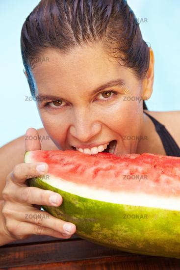 Frau beißt in Melone