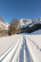 Sunny winter landscape in the nature: Mountain range, footpath, snowy trees, sunshine and blue sky