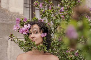Beauty headshot of a young brunette woman with pink flowers outdoors. Shot on 35mm analog cine film.