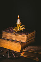 Pile of old antique books with candle and old rusty keys in vintage style on wooden black background