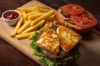 Semi-finished grilled cheese beef burger, served with french fries and tomatoes on a decorative wooden trey with tomato sauce. Fast food concept