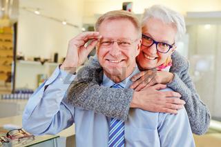 Lachende Senioren mit Brillen beim Optiker
