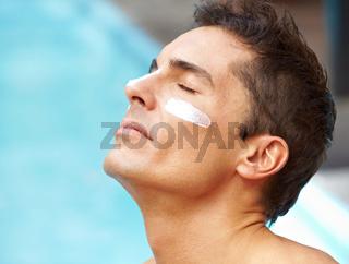 Mann sonnt sich mit Sonnencreme