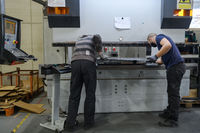 two workers wearing a protective mask due to a coronavirus pandemic, working in a modern factory and preparing a program and materials for a cnc machine