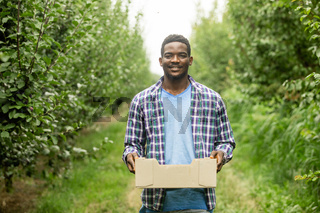 Satisfied farmer holding wooden box with crop