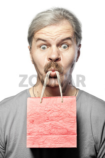 surprised mature man with shopping bag in mouth isolated on white background