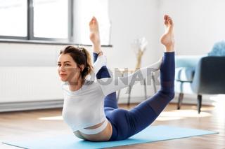 young woman doing bow pose at yoga studio