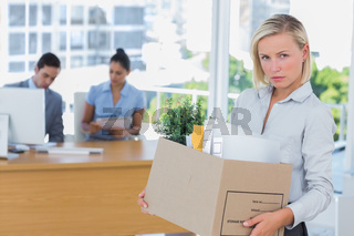 Businesswoman leaving office after being laid off and looking at camera