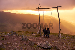 Romantic couple swinging on a Swing baloico in Lousa mountain, Portugal at sunset