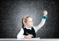 Little girl scientist examining test tube