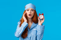 Upset and disappointed cute gloomy redhead girl overslept, forgot set up alarm, holding red clock and frowning, regret watching movies all night, wearing sleep mask and pyjama, blue background