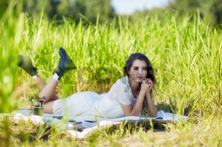 Young blonde woman in white dress lies on a picnic sheet in tall grass.