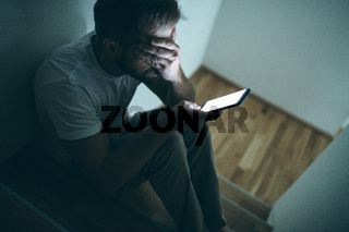 Depressed man sitting in the dark with his smartphone