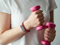 Woman with fitness tracker and barbells