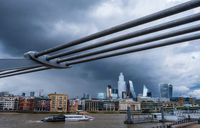 A boat travels on river Thames past the Millennium footbridge with the City of London busines district in the distance set against a dramatic stormy sky.