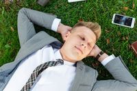 Businessman rests on the grass