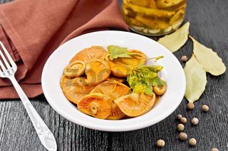 Mushrooms salted in plate on dark board