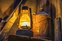 Lit rusty storm lamp and vintage equipment in abandoned workshop or shipyard
