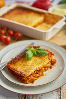 Homemade tasty meat lasagna with fresh basil and parmesan cheese in a plate on wooden background