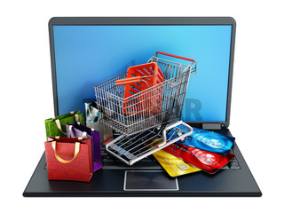 Shopping cart, credit cards and bags standing on laptop computer.