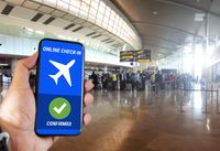 The hand of a man holding a mobile phone with the online check in confirmation message on the screen inside an airport