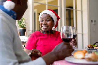 Happy african american senior couple in santa hats making toast with wine at christmas time