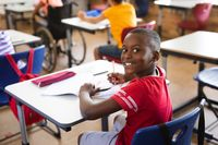 Portrait of african american boy smiling while sitting on his desk in the class at elementary school
