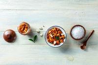 Pickled mushrooms in a jar, with salt, pepper, garlic, a bay leaf, overhead shot