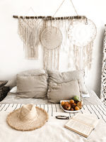 Romantic scandi boho style bedroom interior with wicker hat, fresh fruits and open book on bed