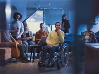 Portrait of disabled businesswoman in a wheelchair in front of her diverse business team at office