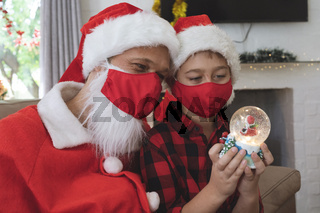 Santa Claus and boy wearing face mask holding snow globe at home