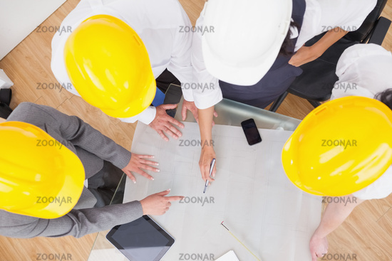 Team looking at a construction plan with hard hats