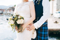 A bride in a wedding dress with bridal bouquet and a groom in a Scottish national dress stand hugging on the pier