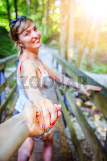 Adventure in the woodland: Girl is holding her boyfriends hand for a new adventure