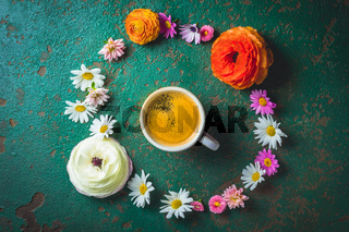 Cup of coffee with variation of flowers on green background with copy space