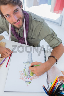 Smiling fashion designer drawing a coat