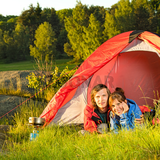 Young couple camping lying in tent