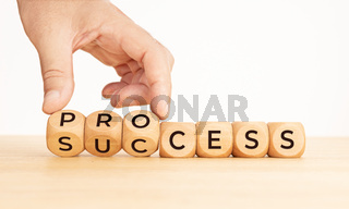 Hand flipping Process to success word on wooden blocks. Copy space
