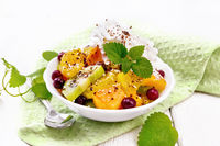 Salad fruit with cranberries in bowl on board