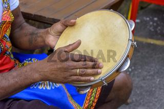 Brazilian samba performance with musician hands playing tambourine