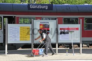 Ein Mitarbeiter der Deutschen Bahn reinigt eine Informationstafel, Wergetafel, Günzburg, Bayern, Deutschland, Europa