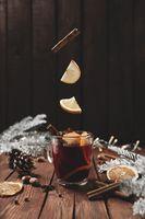 Mulled Wine Christmas cup on table, levitation of cinnamon stick, orange, apple