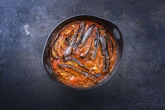 Modern style slow cooked Persian lamb eggplant stew khoresh bademjan served as close-up in a design pot on a rustic board with copy space