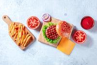 Burger ingredients, overhead flat lay shot. Hamburger patty steak, French fries