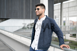 Portrait of a young confident smiling man standing beside modern building looking into the distance
